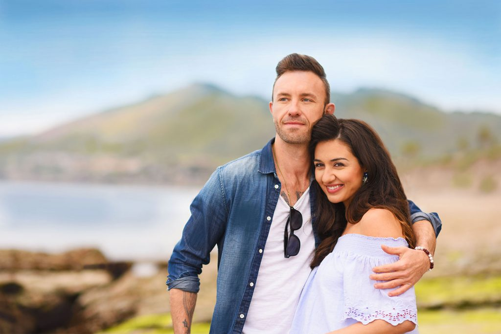 18206-tcr-young-couple-smiling-on-cliffs